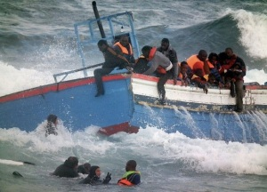 Italian Coast Guard scuba divers, seen bottom left, rescue migrants in Pantelleria, Italy, 13 April 2011.  Officials say two women drowned while attempting to reach Italy from North Africa after their boat with 250 people aboard went off course and ran aground just off an Italian island. Vittorio Alessandro of the Coast Guard said the boat was likely carrying Sub-Saharan Africans as it ran aground on the morning of 13 April 2011 near the small island of Pantelleria. This picture was made available by the Italian Coast Guard.